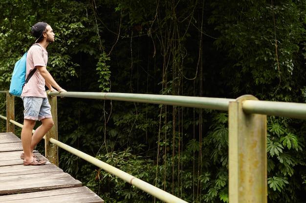 Avontuur en toerisme. knappe blanke student wandelen in het regenwoud. jonge wandelaar met rugzak die zich op houten brug bevindt en groen hout bekijkt
