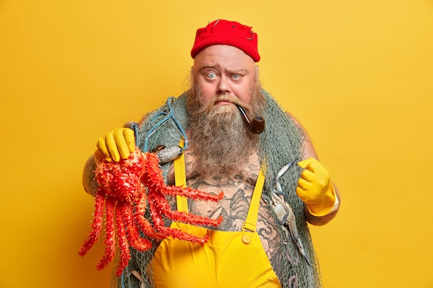 Avontuur, hobby, visserijconcept. boze visser met ernstige strikte uitdrukking balt vuist, toont octopus gevangen tijdens zeereis, fronst gezicht, draagt visnet