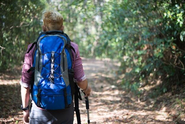 Avontuur jonge man wandelen in de bergen met een rugzak.