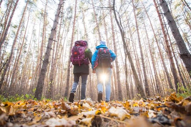 Avontuur, reizen, toerisme, stijging en mensenconcept - glimlachend paar dat met over rugzakken loopt