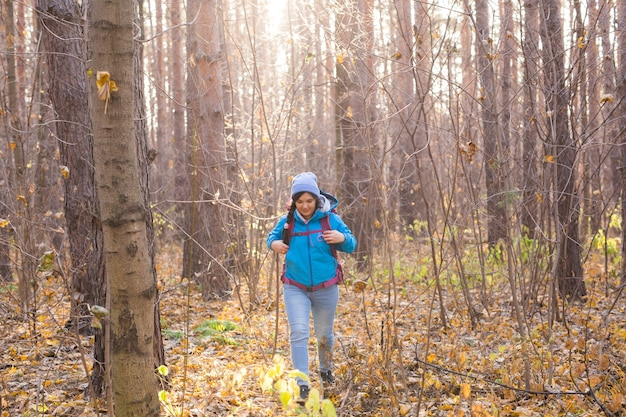Avontuur, reizen, toerisme, stijging en mensenconcept - glimlachende toeristenvrouw die met rugzakken over de herfst natuurlijk bos lopen.