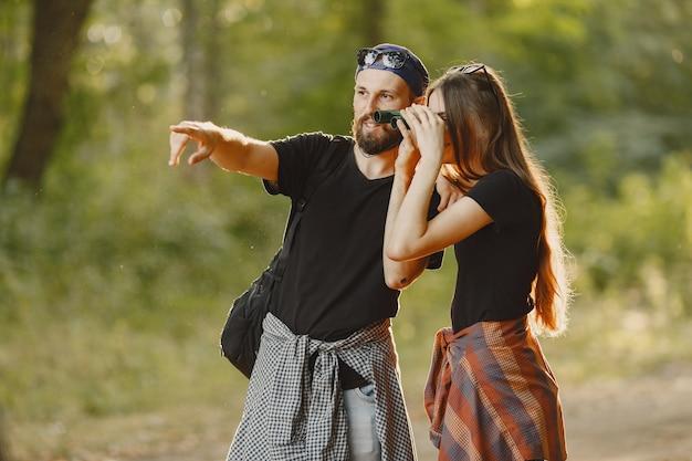 Avontuur, reizen, toerisme, wandeling en mensenconcept. echtpaar in een bos.