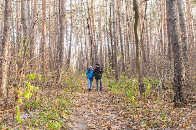 Avontuur, reizen, toerisme, wandeling en mensenconcept - glimlachend paar dat met rugzakken over herfst natuurlijk oppervlak loopt