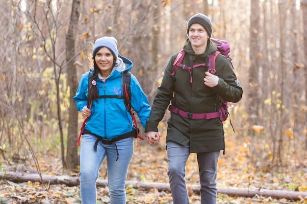 Avontuur, reizen, toerisme, wandeling en mensenconcept - glimlachend paar dat met rugzakken over natuurlijke herfst loopt.