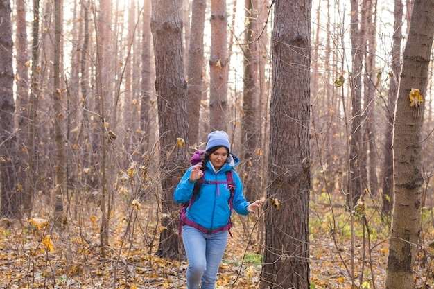 Avontuur, reizen, toerisme, wandeling en mensenconcept - glimlachende toeristenvrouw die met rugzakken over herfst natuurlijk oppervlak lopen.