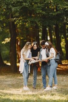 Avontuur, reizen, toerisme, wandeling en mensenconcept. groep lachende vrienden in een bos. man met binocularus.