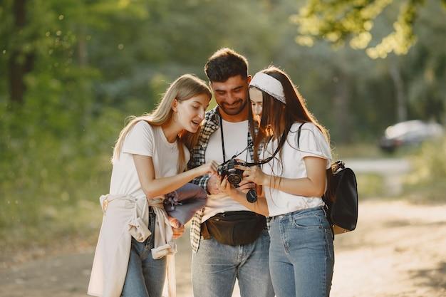 Avontuur, reizen, toerisme, wandeling en mensenconcept. groep lachende vrienden in een bos.