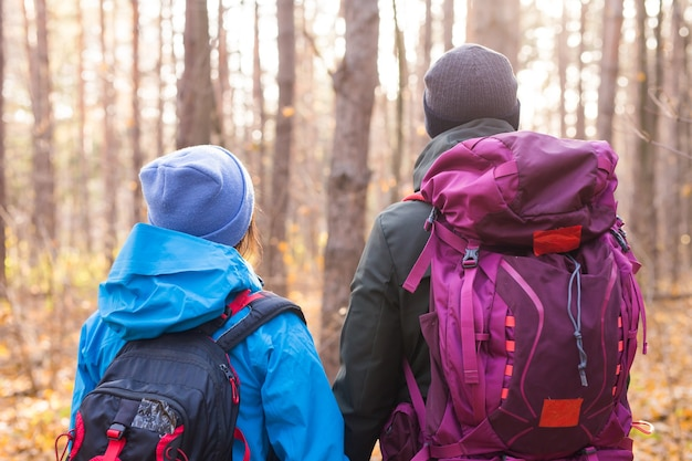Avontuur, reizen, toerisme, wandeling en mensenconcept - paar dat met rugzakken over natuurlijk loopt