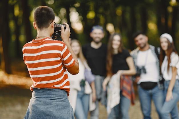 Avontuur, wandeling en mensenconcept. groep lachende vrienden in een bos. guy neemt een foto.