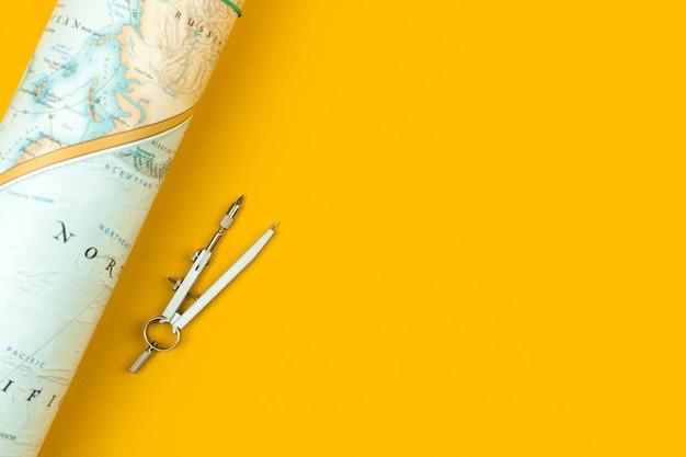 Avontuurconcept met de wereldkaart op de gele bureaubladachtergrond, plat lag bovenaanzicht en kopieer spa...