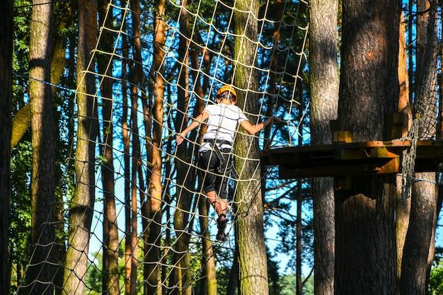 Avontuurlijk klimpark met hoge draad. detailopname. jonge jongen in helm die plezier heeft en speelt in het avonturenpark, touwen vasthoudt en houten trappen beklimt. actief levensstijlconcept. vrijetijdsactiviteiten in de zomer