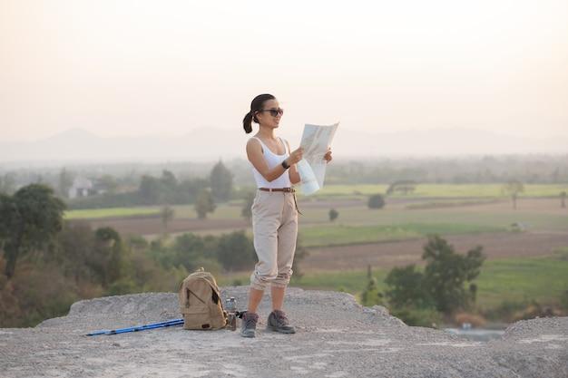 Avontuurlijk meisje navigeren met een topografische kaart in de prachtige bergen.
