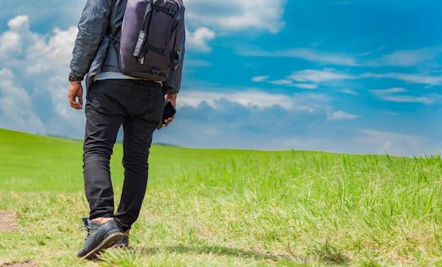 Avontuurlijke man in het veld, man met rugzak in het veld zijwaarts kijkend, close-up van stappen van een jonge backpacker