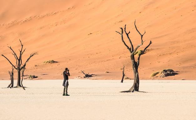 Avontuurlijke reisfotograaf bij deadvlei-krater in sossusvlei namibië