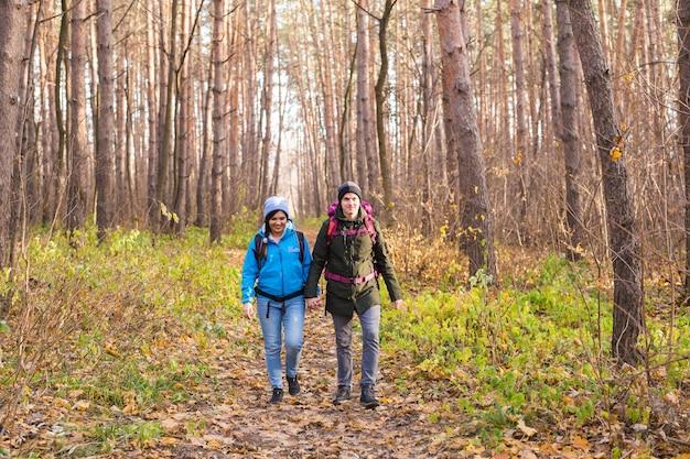 Avontuurlijke reizen toerisme wandeling en mensen concept glimlachend paar wandelen met rugzakken in de herfst