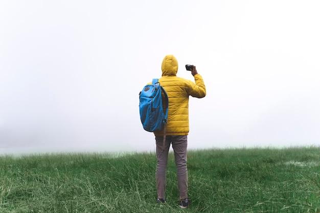 Avontuurlijke wandelaar in de buitenlucht met een gele waterdichte jas die geniet van regenachtig weer