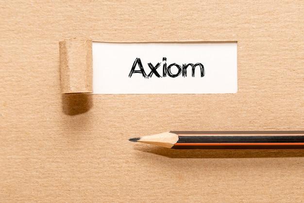 Axiom, tekst op wit papier achter gescheurd bruin papier en potlood