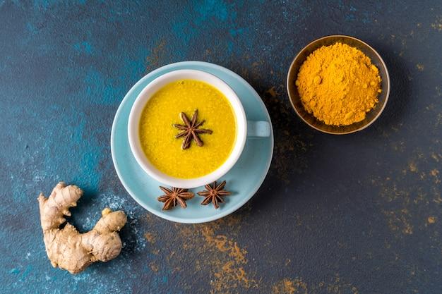 Ayurvedische gouden kurkuma latte melk gemaakt met kurkuma en andere kruiden op blauwe achtergrond. plat leggen.