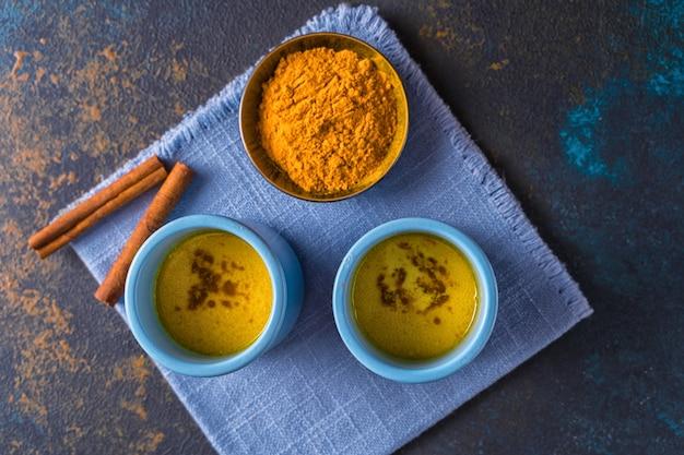 Ayurvedische gouden kurkuma latte melk gemaakt met kurkuma en andere kruiden op houten achtergrond.