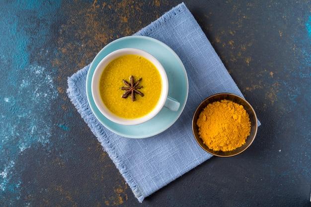 Ayurvedische gouden kurkuma latte melkthee gemaakt met kurkuma en andere kruiden op blauwe achtergrond. plat liggen.