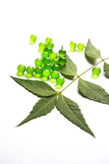 Ayurvedische neem pillen is een oud indiaas medicijn dat wordt gebruikt voor de behandeling van huidaandoeningen en diabetes. geserveerd op een witte achtergrond met verse bladeren