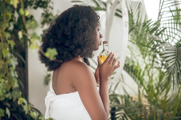 Ayurvedische salon. schattige donkere jonge vrouw met etherische oliën in de hand