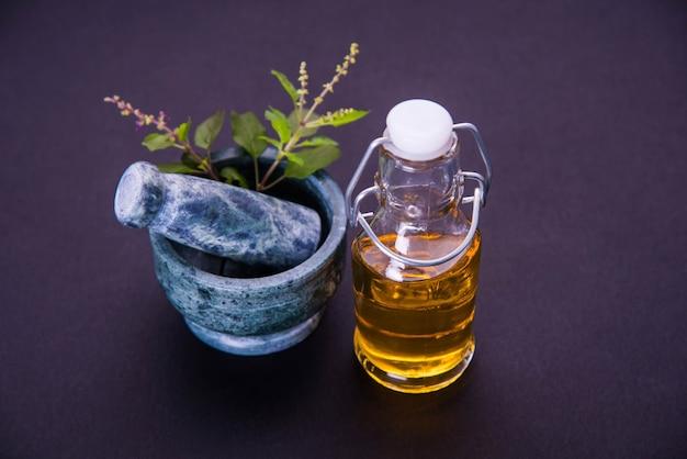 Ayurvedische tulsi-olie, koningin van kruidenextract in glazen fles met verse groene heilige basilicumtakken en vijzel met stamper. geïsoleerd over kleurrijke achtergrond. selectieve focus
