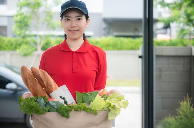 Aziaat bezorgt vrouw die een zak met voedsel behandelt, geeft aan de klant voor het huis
