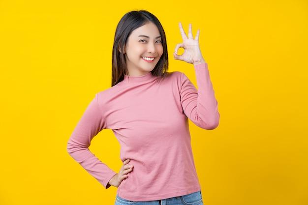 Aziaat die jonge vrouw glimlachen die ok teken voor goedkeuring of overeenkomst over geïsoleerde gele muur gesturing