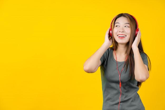Aziaat die jonge vrouw glimlacht die voor het luisteren van musicon geïsoleerde gele muur draagt