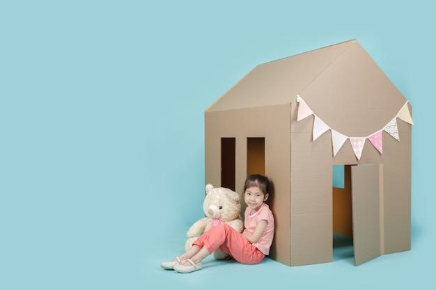 Aziaat klein kindmeisje die met kartonhuis spelen met haar teddybeer die op blauwe lange banner met exemplaarruimte wordt geïsoleerd voor uw tekst, creatief thuis met familieconcept