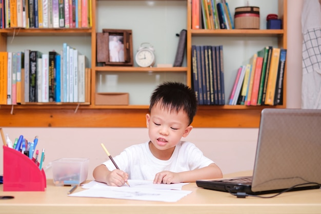 Aziaat weinig jong geitjetekening tijdens zijn online les thuis, afstandsonderwijs, homeschooling concept