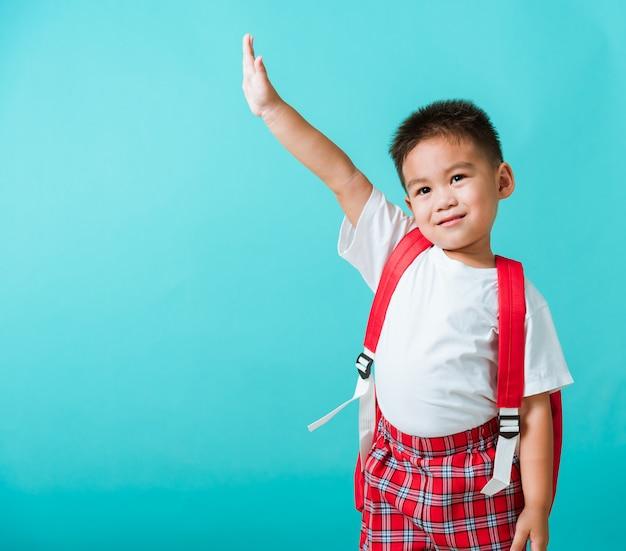 Aziaat weinig kindjongen in eenvormige glimlach heft handen op blij wanneer terug naar school gaat