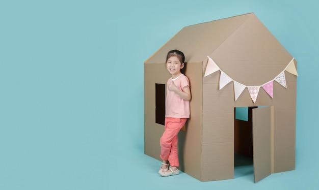 Aziaat weinig kindmeisje die met kartonhuis spelen