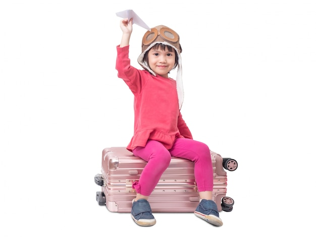 Aziaat weinig leuk meisje 4 jaar oud draagt proefhoed en zittend op roze bagage met holdingsdocument vliegtuig op witte muur wordt geïsoleerd die