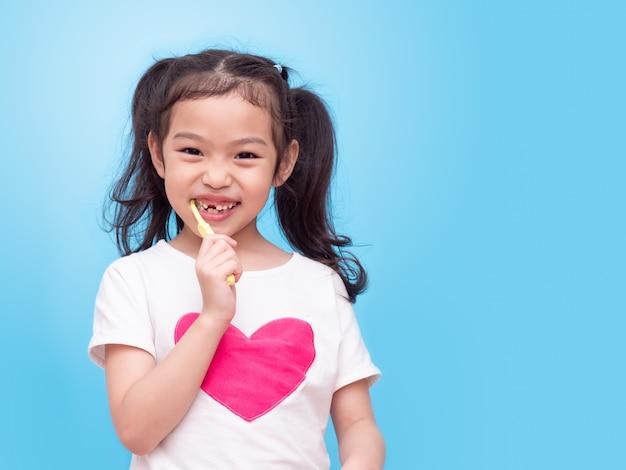 Aziaat weinig leuk meisje dat een gele tandenborstel houdt