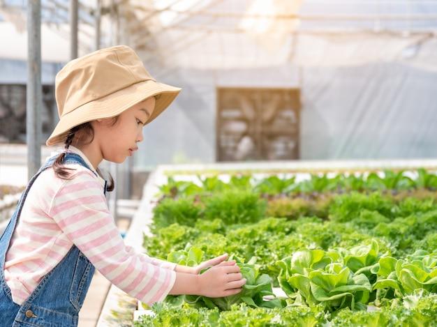 Aziaat weinig leuk meisje dat leert hoe te om groenten bij het hydroponic groene huis te kweken.