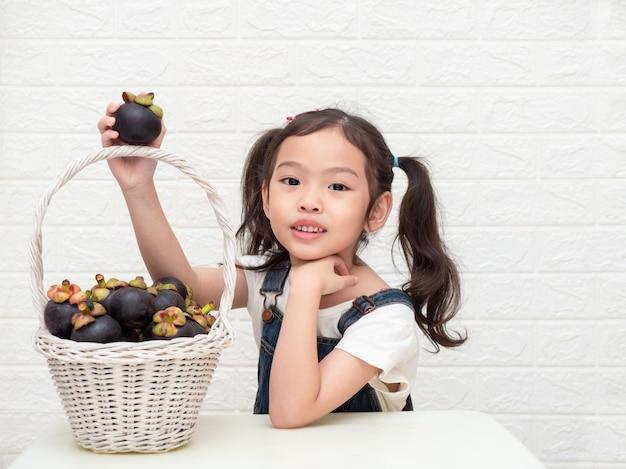 Aziaat weinig leuke meisje en mangostans (mangostana garcinia) in de houten mand op witte achtergrond.