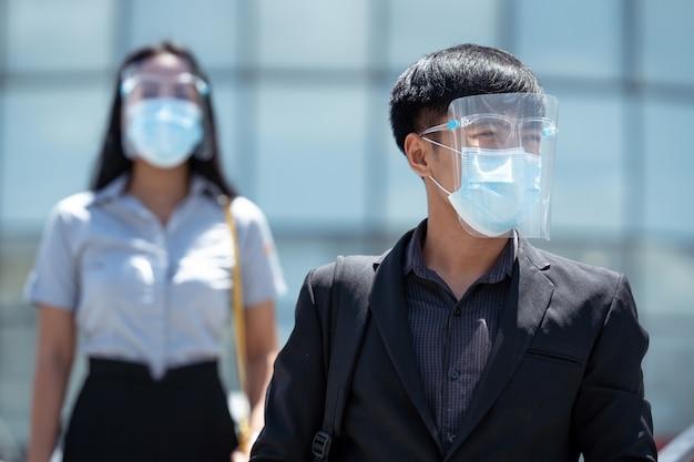 Aziaten worden beschermd door covid 19 en hij draagt een gezichtsmasker.