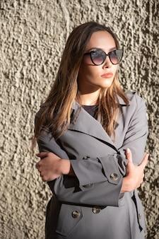 Aziatisch aantrekkelijk model dat trenchcoat en zonnebril draagt die zich dichtbij muur bevindt bij zonnig weer