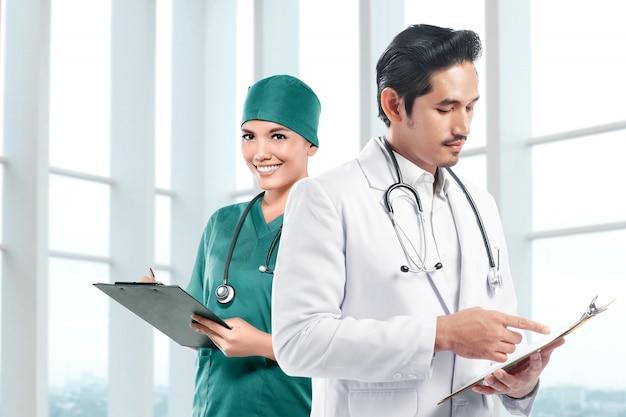 Aziatisch artsenteam dat met stethoscoop een klembord houdt