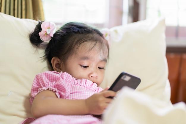 Aziatisch babymeisje die slimme telefoon op het bed bekijken