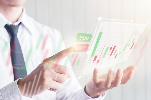 Aziatisch bedrijfsmannetje die vinger wat betreft verkopen knoop op het digitale virtuele scherm met kandelaargrafiek, financieel en investeringsconcept gebruiken