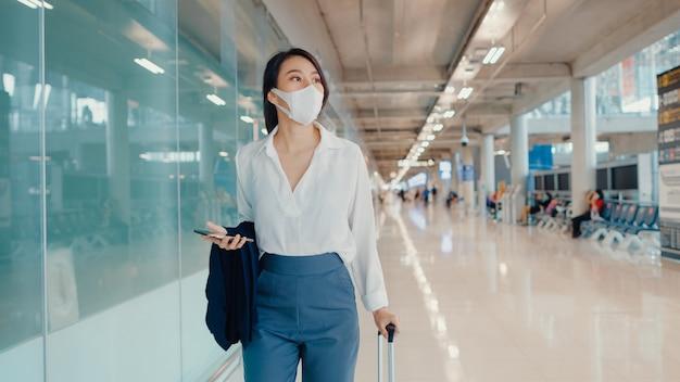 Aziatisch bedrijfsmeisje die smartphone gebruiken voor het controleren van instapkaart die met bagage naar terminal lopen bij binnenlandse vlucht op luchthaven.