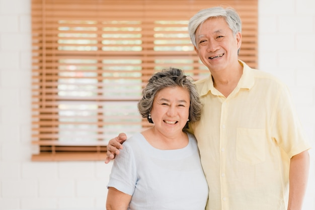 Aziatisch bejaard paar die het gelukkige glimlachen voelen en aan camera kijken terwijl thuis in woonkamer ontspannen.