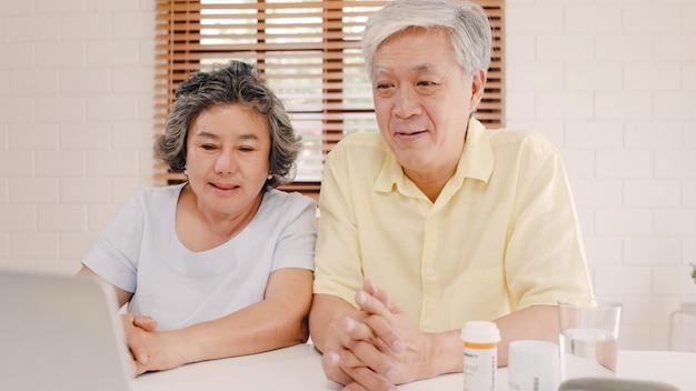 Aziatisch bejaard paar die laptop conferentie met arts over geneeskundeinformatie gebruiken in woonkamer, paar die tijd samen gebruiken samen terwijl het liggen op bank.