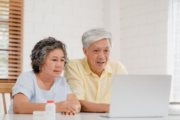 Aziatisch bejaard paar die laptop conferentie met arts over geneeskundeinformatie gebruiken in woonkamer