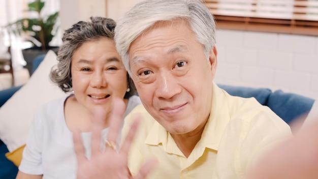 Aziatisch bejaard paar die smartphonevideo conferentie met kleinkind gebruiken terwijl thuis het liggen op bank in woonkamer.