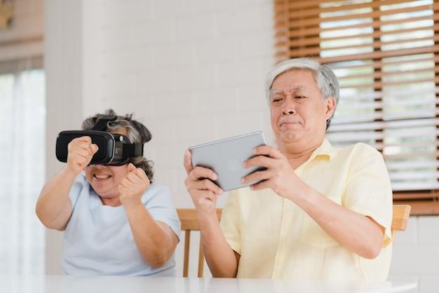 Aziatisch bejaard paar die tablet en de virtuele speeltoestellen van de werkelijkheidssimulator in woonkamer gebruiken