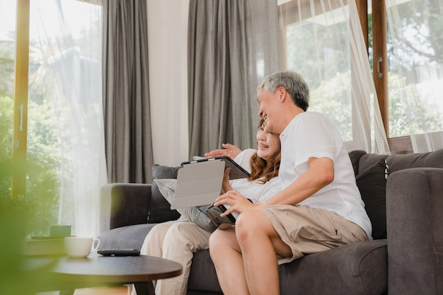 Aziatisch bejaard paar die tablet en de virtuele spelen van de werkelijkheidssimulator spelen in woonkamer, paar die gelukkig gebruikend tijd voelen die samen op bank thuis liggen. lifestyle senior familie thuis concept.